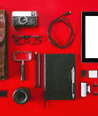 Closeup of different photography objects on red background overhead essentials in order Royalty Free Stock Photo