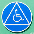 Closeup of a disabled sign on green wall Royalty Free Stock Photo