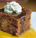 Closeup english toffee pudding topped vanilla whipped cream white plate Stock Image