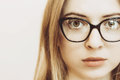 Closeup of and eye of blonde woman with black glasses Royalty Free Stock Photo