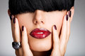 Closeup face of a woman with beautiful sexy red li lips and dark nails studio Stock Images