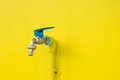Closeup faucet on concrete Yellow wall background. Water leaking Royalty Free Stock Photo