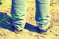 Closeup of feet of a man in old blue jeans and old shoes. Tinted. Royalty Free Stock Photo