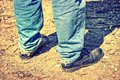 Closeup of feet of a man in old blue jeans and worn-out shoes. T Royalty Free Stock Photo