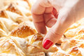 Closeup of female hand reaching for pastry a freshly baked frankfurter sausages battered in puffed french Royalty Free Stock Image