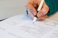 Closeup of female hand signing document in blue sweater with black pen Royalty Free Stock Photo