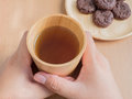 Closeup of female hands holding wood cup of Organic Jasmine Tea with cookies Royalty Free Stock Photo