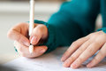 Closeup of female hands signing document in blue sweater with black pen Royalty Free Stock Photo