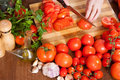 Closeup of female hands slicing tomatoes in kitchen Stock Image