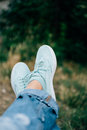 Closeup of female legs in jeans and sneakers on a background of trees Royalty Free Stock Photo