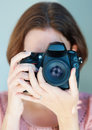 Closeup of a female photographer with a SLR camera Royalty Free Stock Image
