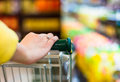 Closeup of female shopper with trolley at supermarket Royalty Free Stock Photo
