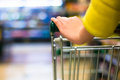 Closeup of female shopper with trolley at supermarket Stock Image