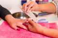 Closeup females hands getting manicure treatment from woman in salon environment, pink towel surface, blurry background Royalty Free Stock Photo