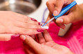 Closeup females hands getting manicure treatment from woman using small brush in salon environment, pink towel surface Royalty Free Stock Photo