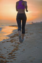 Closeup on fitness young woman running on beach in the evening sportswear Stock Photos