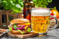Closeup fresh burger cold beer old wooden table Royalty Free Stock Images