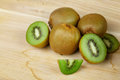 Closeup of fresh green kiwi lying on a light wooden table, slice of kiwi, piled kiwi on a light wooden table. Royalty Free Stock Photo