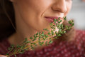Closeup of fresh thyme being smelled by an elegant woman in this breathes in the earthy smell holding it up against her mouth Stock Photo