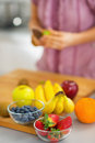 Closeup on fruits on cutting board and housewife in background young Royalty Free Stock Photography