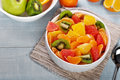 Closeup fruits salad in plate on blue wooden table Royalty Free Stock Photo