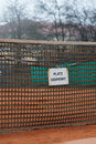 Closeup german tennis court platz gesperrt or closed sign hanging from net of clay Stock Photos