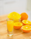 Closeup on glass of orange juice and oranges on cutting board in kitchen Stock Photos