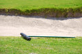 Closeup of a golf course sand trap and rake detail bunker with rich green grass on on sunny day Stock Images