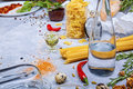 Closeup of a gray table with pasta, glass bottle, red chili pepper, quail eggs and walnuts on a gray background.