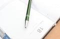 Closeup of green pen on notebook organizer lying open a desk Stock Photos