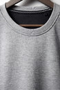 Closeup of grey jumper blank hanging on white wall Royalty Free Stock Photography