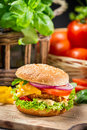 Closeup hamburger chicken fresh vegetables old wooden table Royalty Free Stock Image