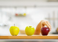 Closeup on hand choosing between two green and one red apple cutting board Stock Images