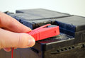 Closeup hand plug car battery red clamp plus of automobile charger on accumulator Royalty Free Stock Image