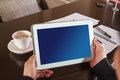 Closeup of hand and tablets digital tablet with blue screen in coffee shop Stock Photography