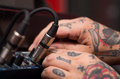 Closeup of hands covered with tattoos working on cable connection hardware audio box, studio equipment concept Royalty Free Stock Photo