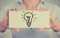 Closeup hands holding sign with hand drawn illuminated light bulb Royalty Free Stock Photo