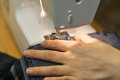 Closeup of hands a yong woman on the sewing machine, stitching t