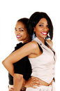 Closeup of happy girls a pictures two girlfriends standing back to back for white background smiling into the camera Stock Photography