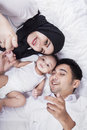 Closeup of happy parents and baby boy unique perspective lying on bed with their while looking smiling at the camera Royalty Free Stock Photos