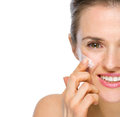 Closeup on happy woman applying creme on cheek young Stock Photos