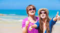 Closeup of happy young couple in sunglasses smiling thumbs up this image has attached release Royalty Free Stock Images