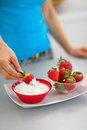 Closeup on happy young woman eating strawberry with yogurt in kitchen Stock Photography