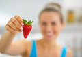 Closeup on happy young woman showing strawberry fresh Stock Images