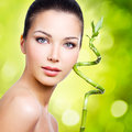 Closeup healthy face of young woman with sprout in hands over nature green background Stock Photo