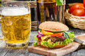 Closeup homemade burger cold beer old wooden table Royalty Free Stock Photography