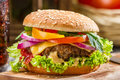 Closeup of homemade hamburger with fresh vegetables on old wooden table Stock Images