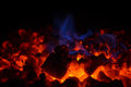Closeup of hot red embers and blue flame in fireplace Royalty Free Stock Photo