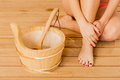 Closeup human woman legs feet and sauna bucket. Royalty Free Stock Photo