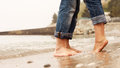 Closeup image couple legs at the beach barefoot Royalty Free Stock Photo
